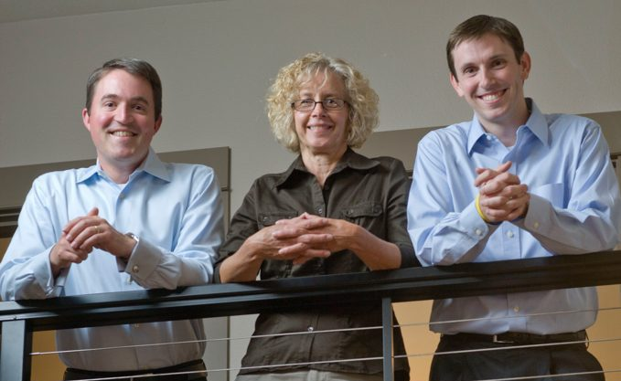 Three Flagler Law Group employees standing by rail